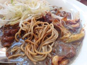 黒いスープの担々麺に甘めの回鍋肉が乗ってくる